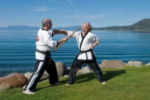 Two men practice martial arts on the shore of Lake Tahoe.